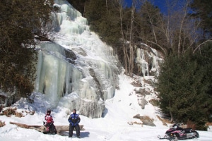 Snowmobilers in front of icicle rock cut